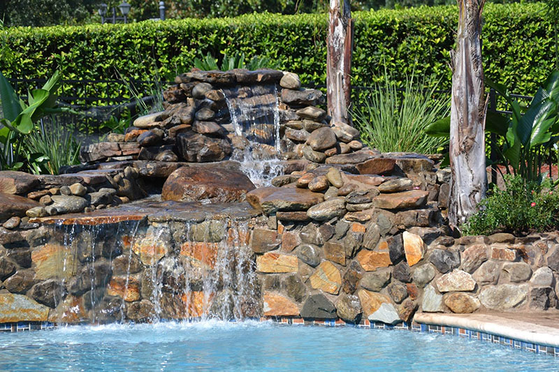 Beautiful waterfall made from stone for a large inground pool
