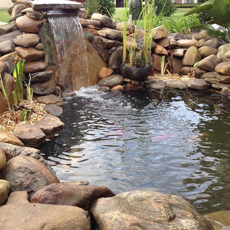 Natural stone pond with waterfall and landscaping