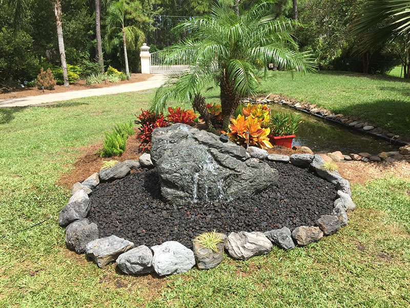 Natural stone waterfall, pond and landscaping by Earth Source Jax